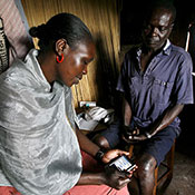 Researcher seated across from a patient enters data on a mobile device.