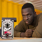 Photo courtesy of Royal Academy of Engineering. Brian Gitta observes a malaria detection prototype.