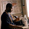Researcher wearing scrubs in lab prepares samples, microscope in background, poster on wall reads Malaria