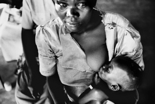 A black and white photo of an African woman nursing her baby
