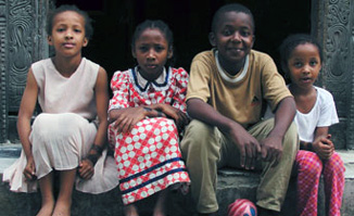 Four Tanzanian children sit together on a step