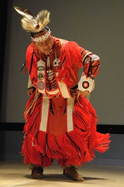Native American man in traditional dress, including a feathered headdress, a red fringed robe and moccasins, performs dance