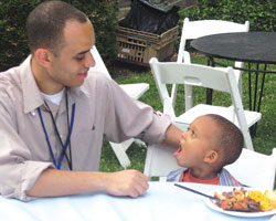 Photo: Dr. Gerald Bloomfield seated next to a 3-year-old boy at a picnic table