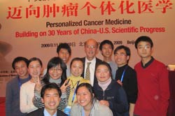 PHOTO: A large group of 11 smiling Chinese researchers, a mixture of men and women, stand around Dr. Roger Glass