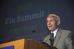 NIAID Director Dr. Anthony Fauci speaks at a podium, on screen in background a slide reads 2009 Flu Summit www.flu.gov