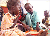 PHOTO: a girl and boy child eat with their hands from a large bowl