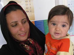 A woman with a headscarf on holds and looks at a baby, the baby looks at the camera, both are in front of a bulletin board