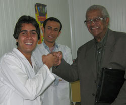Iranian male doctor in lab coat shares a fist bump with Dr. Aaron Shirley, another Iranian male doctor observes