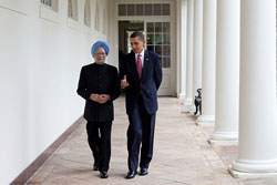 Indian Prime Minister Singh and U.S. President Obama walk side-by-side along a corridor, speaking to each other