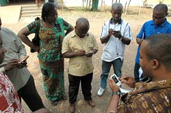 Man leads a discussion holding a handheld device, while a group of 6 additional people follow along on their own devices