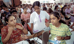 Photo: A Sri Lankan woman has her blood pressure checked by a health education nurse in a crowded clinic