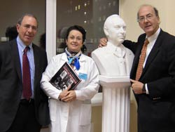 PHOTO: Dr. John I. Gallin, Prof. Elena N. Baibaraina and Dr Roger Glass stand together, Dr. Glass with his arm around a bust