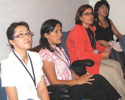 Photo: Four women scholars, seated, attentively listen to speaker