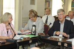 Dr. Francis Collins, seated at a panel table in a conference room to the right of two women, speaks into a microphone