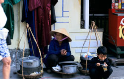 Photo: a Vietnamese woman and child crouche next to pots on the sidewalk