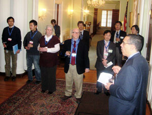 A group of reception attendees look on as Dr. Michael Johnson speaks.