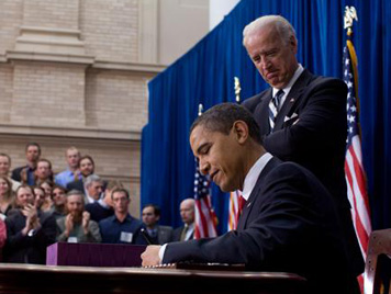 President Obama signing the Act while Vice President Joe Biden looks on.