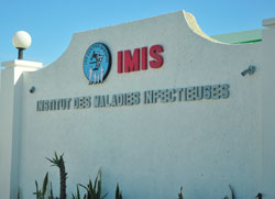 Photo: Outside of tan buliding, GHESKIO's second site, sign reads 'IMIS / Institut des Maladies Infecteuses'