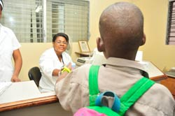 Photo: a child with his back to the camera hands a sample to a nurse behind a desk