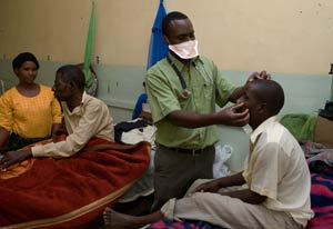 Photo: male doctor wearing a facemask, standing, examines a male patient, seated on hospital bed