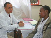 Photo: Dr. Gerald Bloomfield speaks to young male patient, both seated, a table covered with papers between them