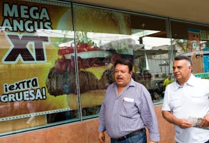 Photo: Large sign picturing fast food hamburger reading Mega Angus XT in window on street, two men walk past