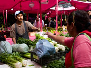 Photo: at outdoor vegetable market woman facing away from camera reaches across a table full of leafy green vegetables