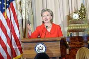 Photo: Hillary Rodham Clinton speaks from behind a podium, US flag to her right
