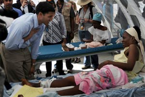 Photo: Rajiv Shah leans in to speak to a Haitian woman on an a hospital bed whose leg is bandaged and braced