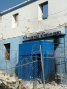 outside of concrete building, sign over door reads Prison Civile de Port-au-Prince, rubble covers ground