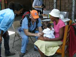 PHOTO: Hatian woman holding young child in her lap, seated next to male doctor in blue scrubs and a baseball cap