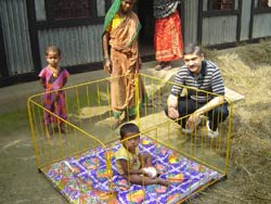 PHOTO: Dr. Hydner squats next to a toddler in a yellow metal playpen, another toddler and two women in wrap dresses look on