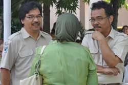 Photo: Dr Irmansyah and another man, both dressed in tan uniform shirts and facing camera, speak to woman with green head scarf