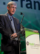 Dr Francis S Collins speaks into microphone at podium, sign reads mHealth Summit on front of podium