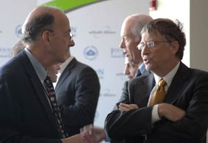 Dr Roger I Glass speaks with Bill Gates, crowded exhibit hall in background