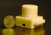 Small, white lens-free microscope, pictured alongside a quarter, which is about half the height of the microscope