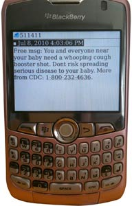 close up of Blackberry smart phone showing 5-line text message about whooping cough