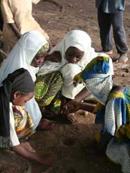 Photo: Four young Nigerian girls with scarves on their heads squat, and play and dig in the dirt with their hands