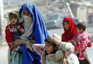 Two Pakistani women with colorful scarves wrapped around their heads walk carrying toddlers, older boy walks beside them