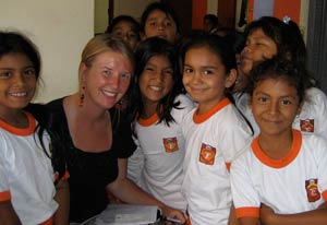 Photo: Catherine Pastorius seated surrounded by many young Peruvian girls in soccer jerseys, all smiling.