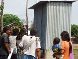 Photo: Many people, including women holding toddlers, gather around a small corrugated metal outhouse