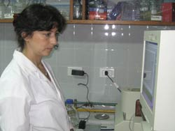 Photo: Dr Rajal in a lab coat looks at a computer monitor in a laboratory