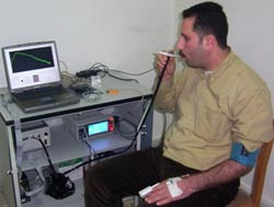 Man seated in chair observes computer screen and equipment as he inhales on a cigarette