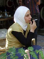 PHOTO: woman, seated, with head scarf, smokes ciagrette