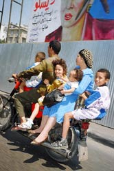 PHOTO: family of father, mother, and four children ride on a small scooter