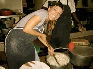 Dr. Elizabeth Vaughan, smiling, stirs large metal pot full of white porridge with large wooden spoon