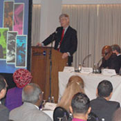 Dr Francis Collins speaks at a podium in front of full conference room