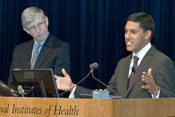 Dr. Rajiv Shah speaks into microphone at podium, Dr. Francis Collins stands next to him