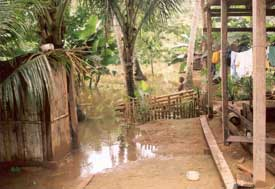 Wooden latrine immersed in shallow flood waters just feet from covered porch
