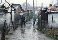 Muddy path full of puddles between shantys in a ghetto in Sophia, Bulgaria, rain falls, two people run away from camera